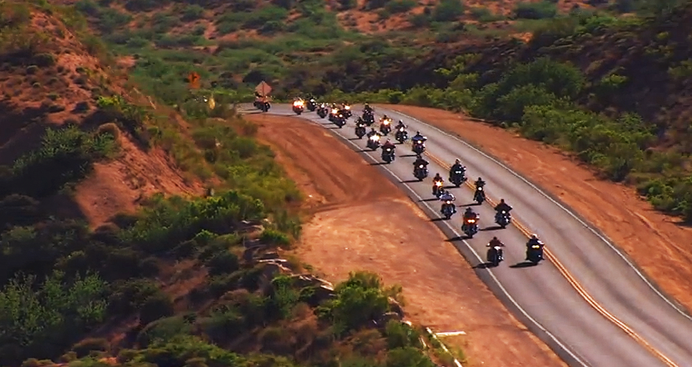 "From the Dierks Bentley video, ""Ride On"", a pcture of many motorcycles on a hilly desert highway."